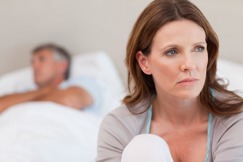 How to decrease testosterone — Sad mature woman on bed with her husband in the background