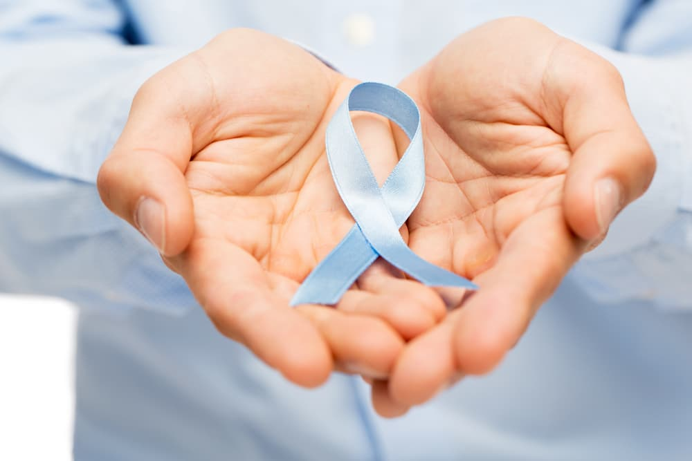 The cause of prostate cancer is not well understood. hands with blue prostate cancer awareness ribbon