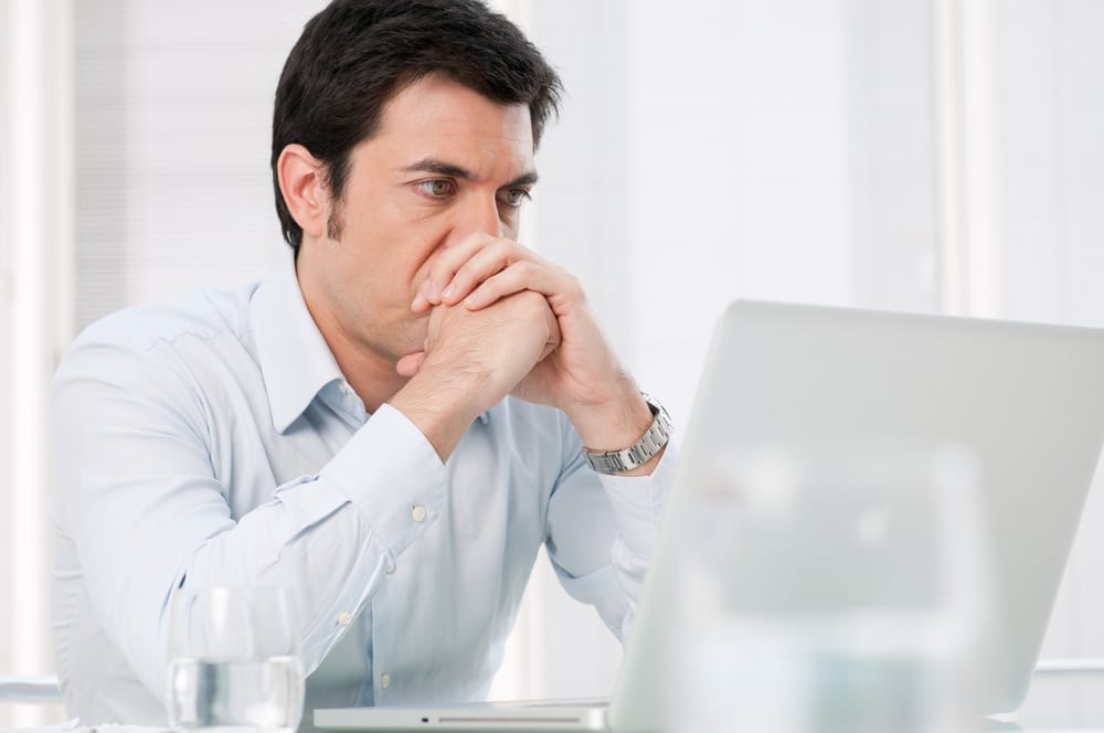 Does a vasectomy hurt? Pensive man researching vasectomies with a worried expression
