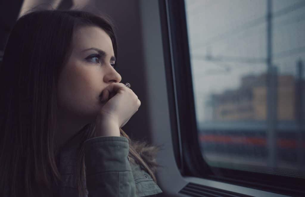 A dark-haired woman stares out the window of a train at the overcast city, perhaps worried about Low T in women.