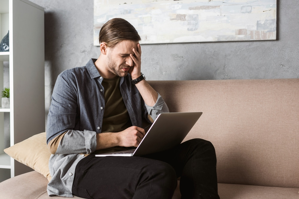 A man in a gray shirt rubs his face with his left hand while sitting on a brown sofa. He has a laptop computer on his lap. He looks exhausted, and he's possibly considering a Low T test at the TCT Frisco clinic.