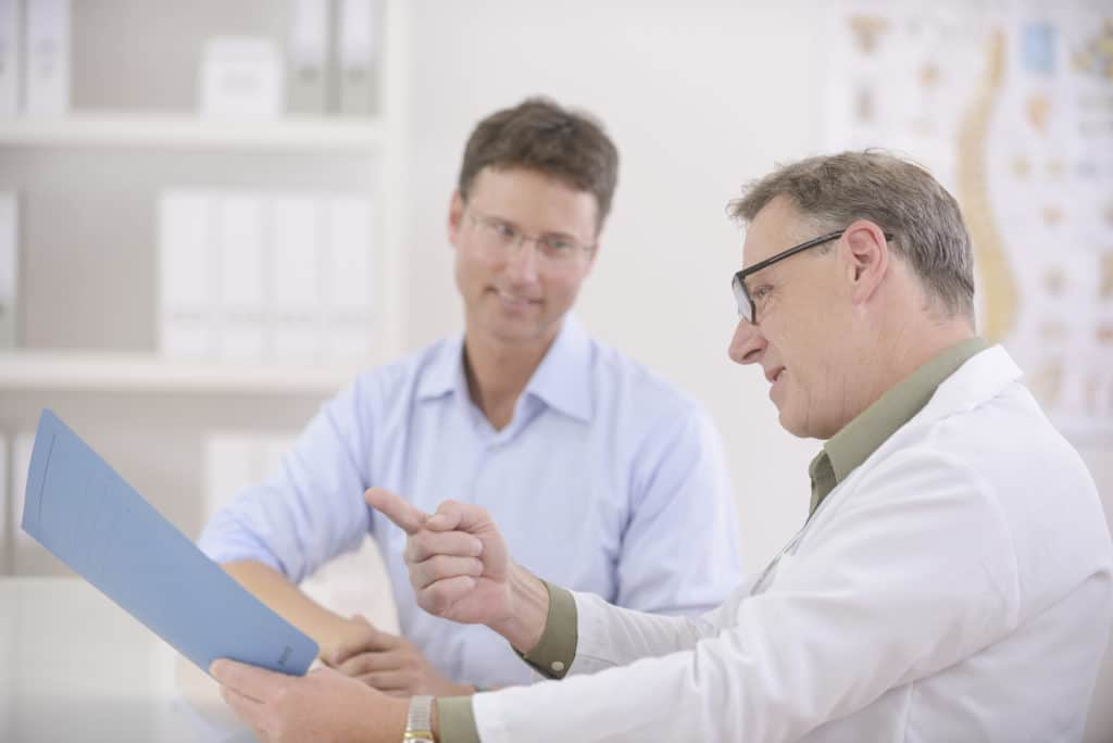 A doctor wearing a white lab coat and glasses discusses with a smiling male patient the results of a low T test at the Prosper clinic.