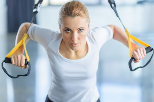 A woman exercising on a machine with a look of intense effort. The best exercises for hormonal imbalance are the same for both men and women. Learn more.