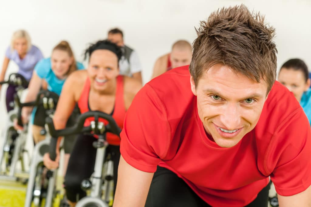 A smiling man in a red t-shirt leads a spin class. Learn about the many exercise trends in Flower Mound.