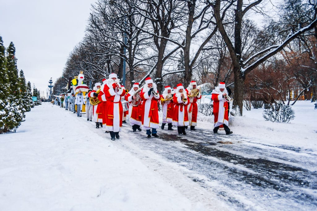 A parade of Santas playing musical instruments marches through a snow-covered park. A Christmas parade is one of the annual holiday events held in Frisco.
