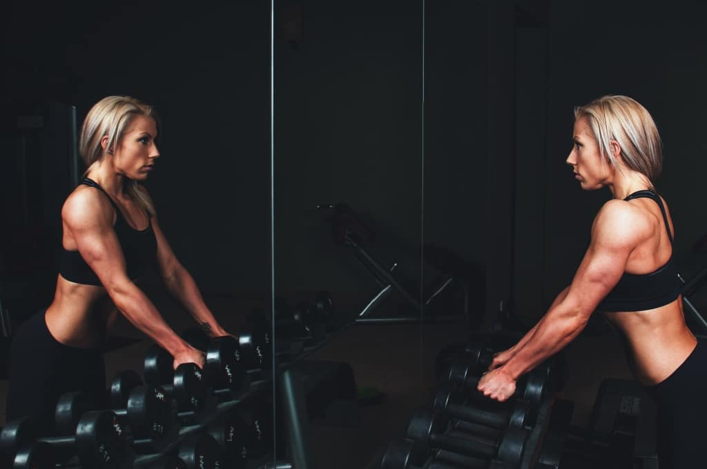 A woman lifting weights in her home gym. Starting a home fitness routine doesn't have to be so difficult. Here's how you can get started.