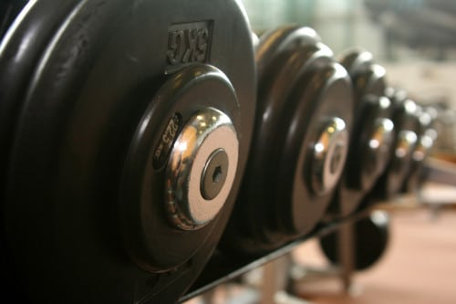 Weights in a rack. Bodybuilding can be severely hindered if you suffer from Low T. Learn more.