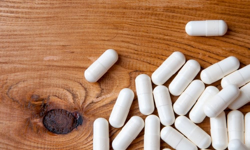 White pills on a wooden table that could resemble sublingual testosterone. Sublingual testosterone is generally not recommended. Here's why.
