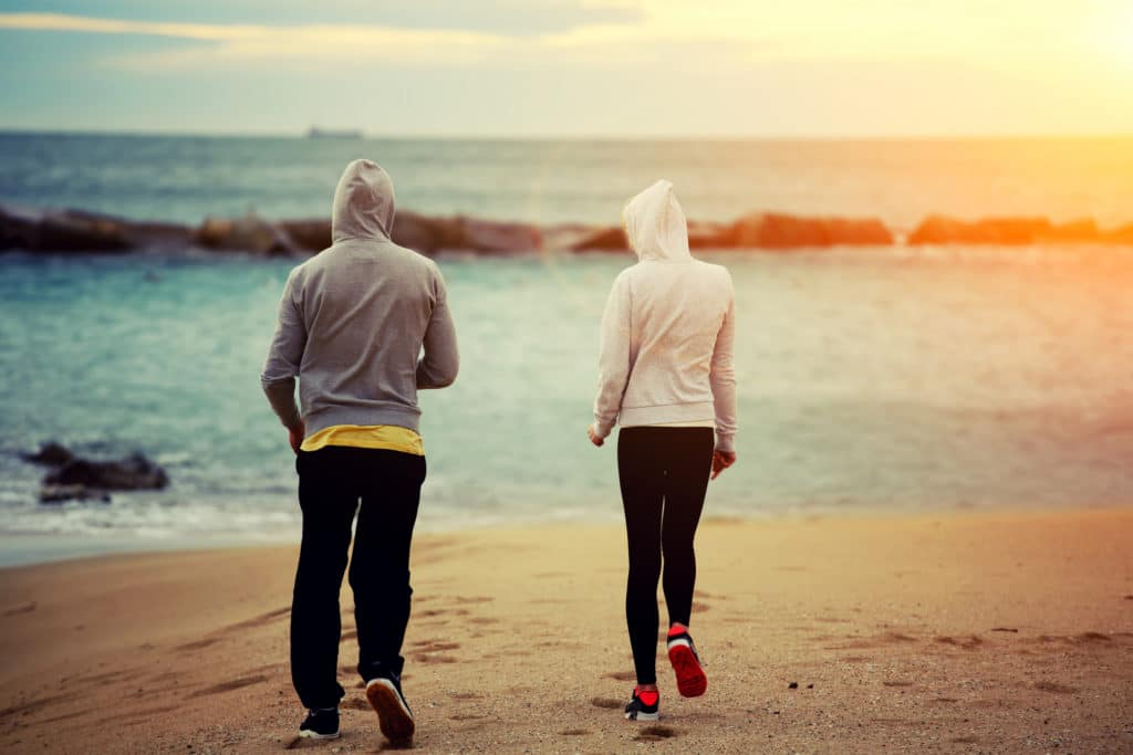 A man and woman wearing hooded sweatshirts and long pants are practicing workplace wellness strategies by taking a walk on the beach.