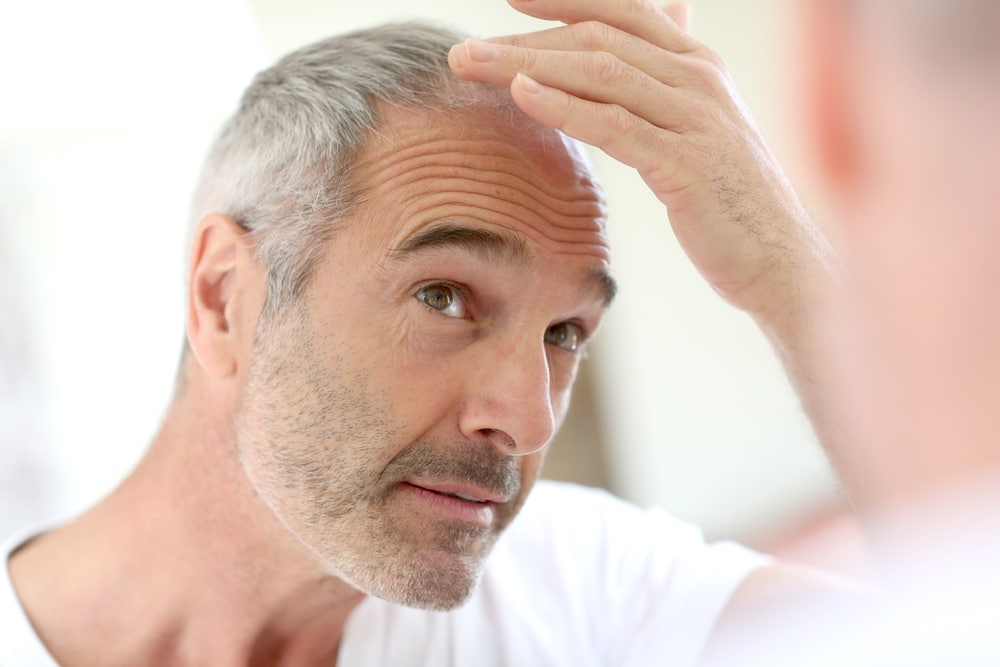 A balding man checking his baldness in the mirror. Testosterone Replacement Therapy will not make you go bald. Learn more.