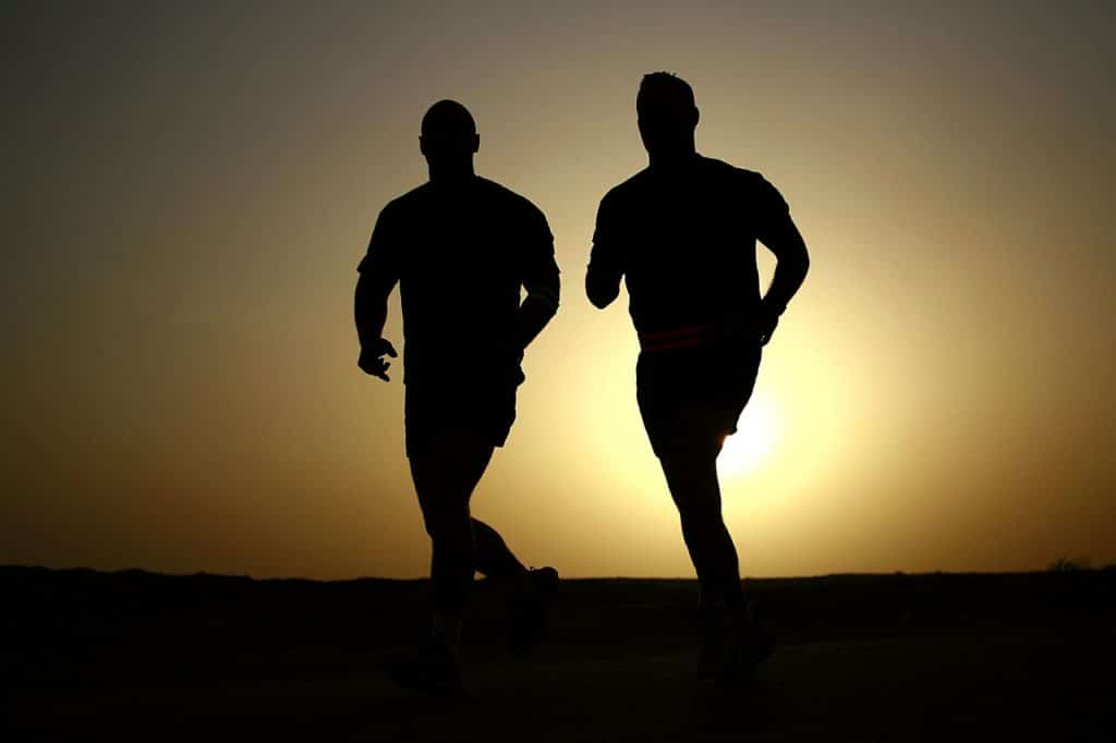 Two shadowed men running in the early morning with the sun rising behind them. Does running increase testosterone?