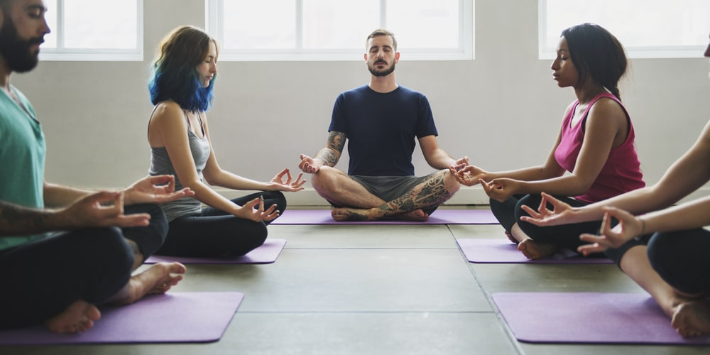 Five people sit in a semi-circle, practicing Yoga in the lotus position. Yoga is one of our recommended activities to reduce stress in Frisco.