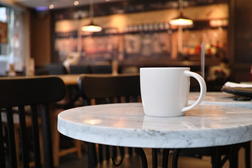 A white ceramic coffee mug sits on a small marble table, possibly in a wood-appointed coffee shop in Lewisville.