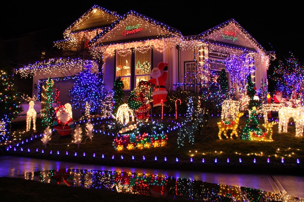 Christmas lights in many colors decorate a large house, and a reflection of the display can be seen in water in the foreground. Viewing holiday lights is one of the many holiday events in Prosper.