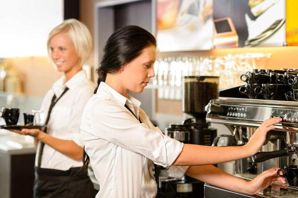 2 female baristas wearing white shirts make coffee drinks at an espresso machine, possibly at a coffee shop in Hurst.
