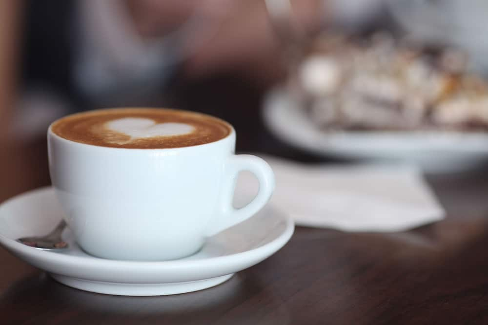 A white coffee cup filled with coffee and a heart-shaped froth design sits in a saucer on a dark wood table, possibly in a Frisco coffee shop.