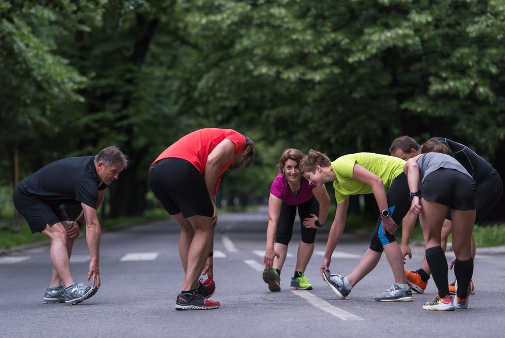 A circle of local runners stretch their hamstrings on a park road, possibly one of the free Lewisville meetups available.