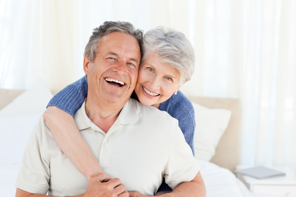 And older man and his wife laughing on a bed. Low testosterone and erectile dysfunction are closely linked. Learn more about how these two issues are related.