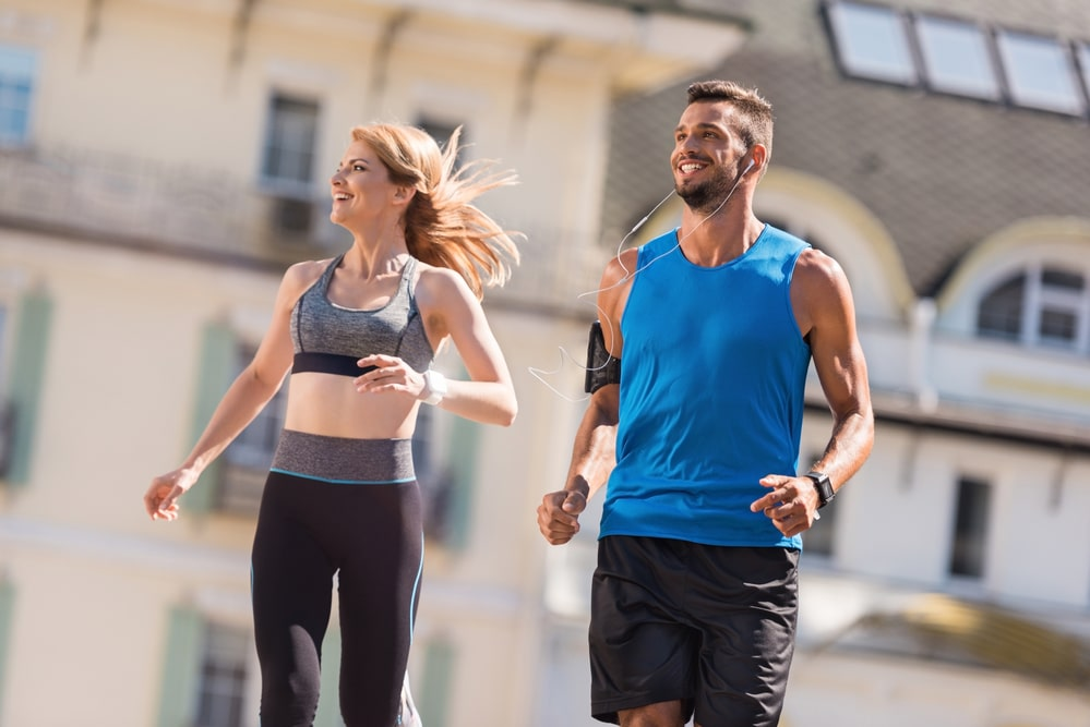 A woman and a man are jogging in the city. They are visibly enjoying themselves, possibly participating in a 5K race near Hurst.