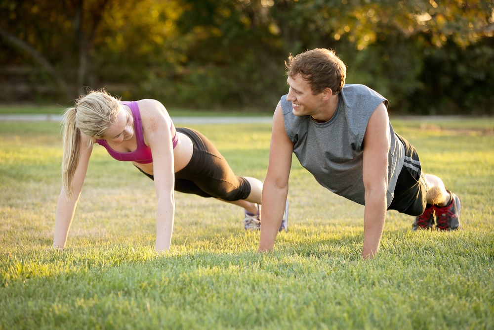 A blonde woman and light-haired man wearing exercise apparel are doing planks in the park, possibly as part of one of the many free exercise classes in the DFW area.