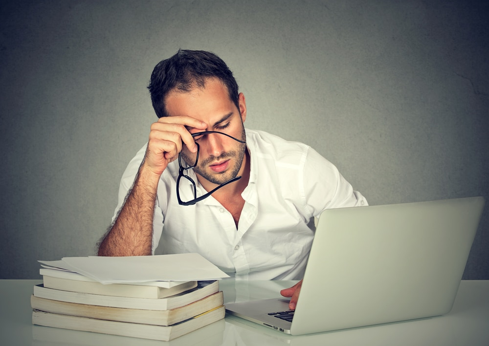 A middle-aged man wearing a white shirt sits at a white table, working on a laptop computer. He has a pile of books and files at his right elbow. Apparently suffering burnout, he has removed his glasses and is rubbing his brow.