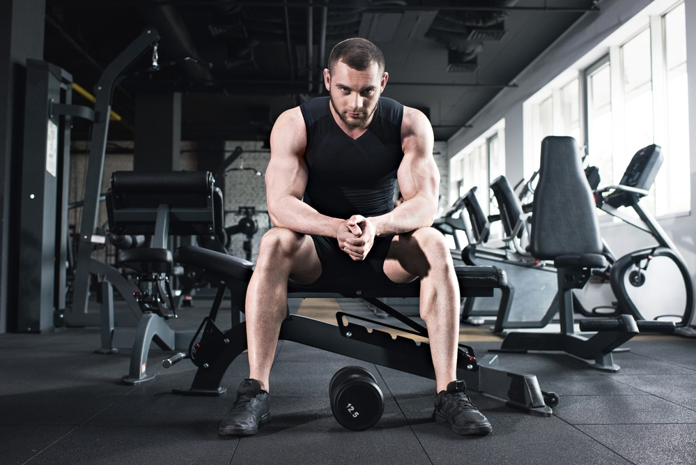 A man with short hair wearing a black tank top sits on a weight bench with a dumbbell between his feet. He may be wondering: Is testosterone a steroid?