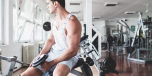 A middle-aged man in a white tank top is sitting on a weight bench while holding a dumbbell in his left hand. He seems puzzled, possibly wondering if testosterone is a steroid.