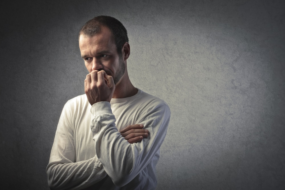 Un uomo in camicia bianca a maniche lunghe e capelli corti si stringe il pugno alla bocca, riflettendo su un'idea difficile, forse il ruolo degli estrogeni negli uomini.