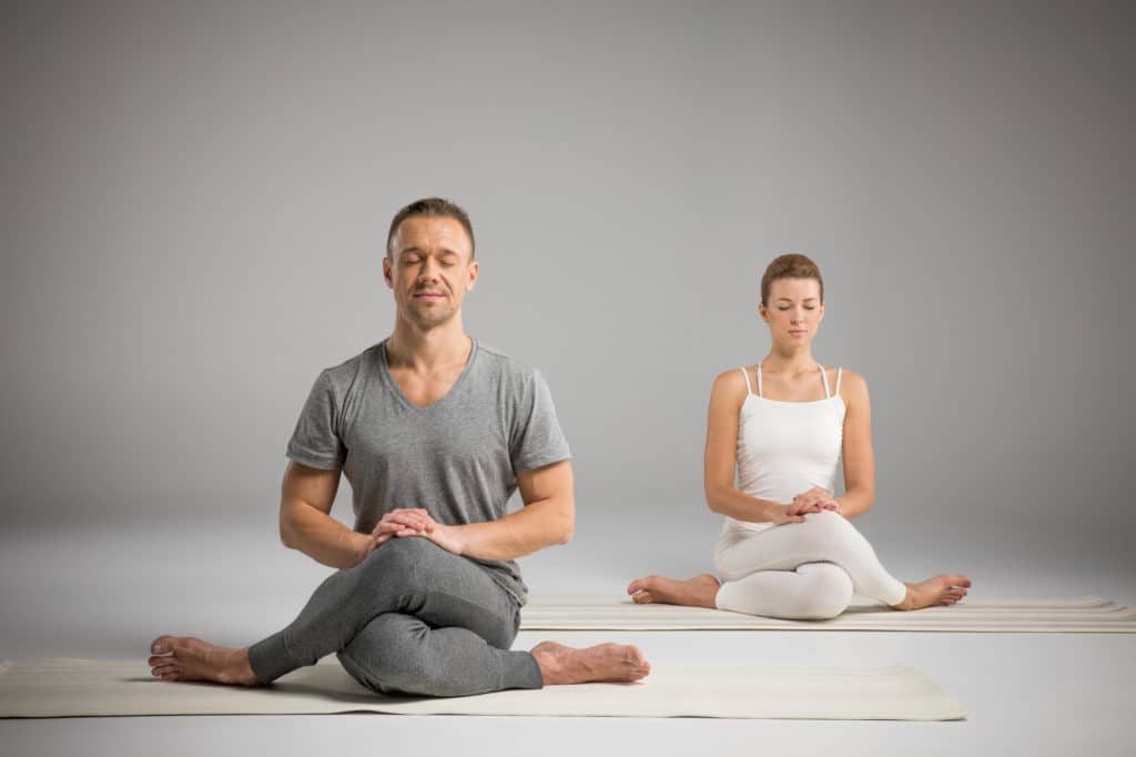 A man in gray and a woman in white sit cross-legged as they practice meditation and mindfulness at a DFW studio.