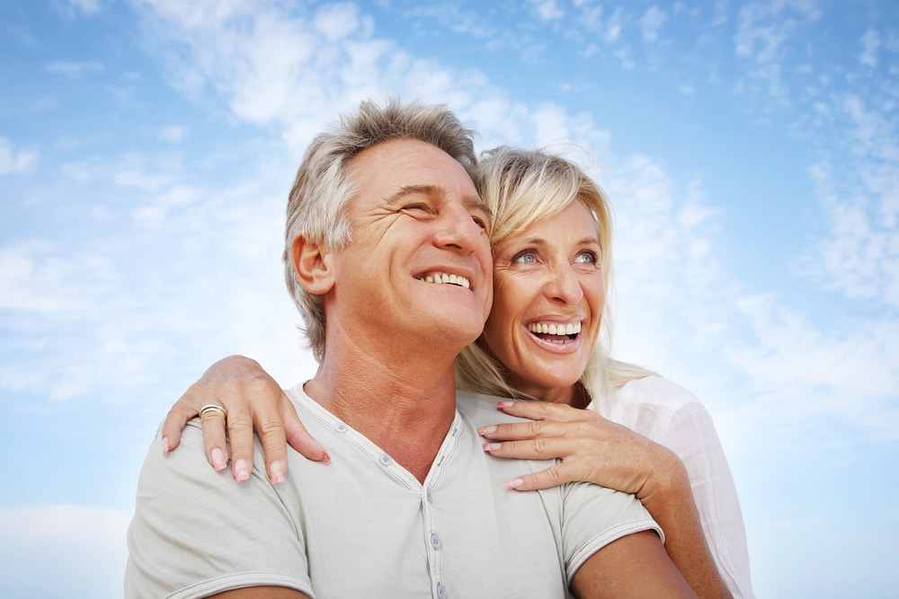 A happy couple is pictured against a blue sky. They are smiling, and the woman may be feeling better as a result of treatment for low estrogen in women.