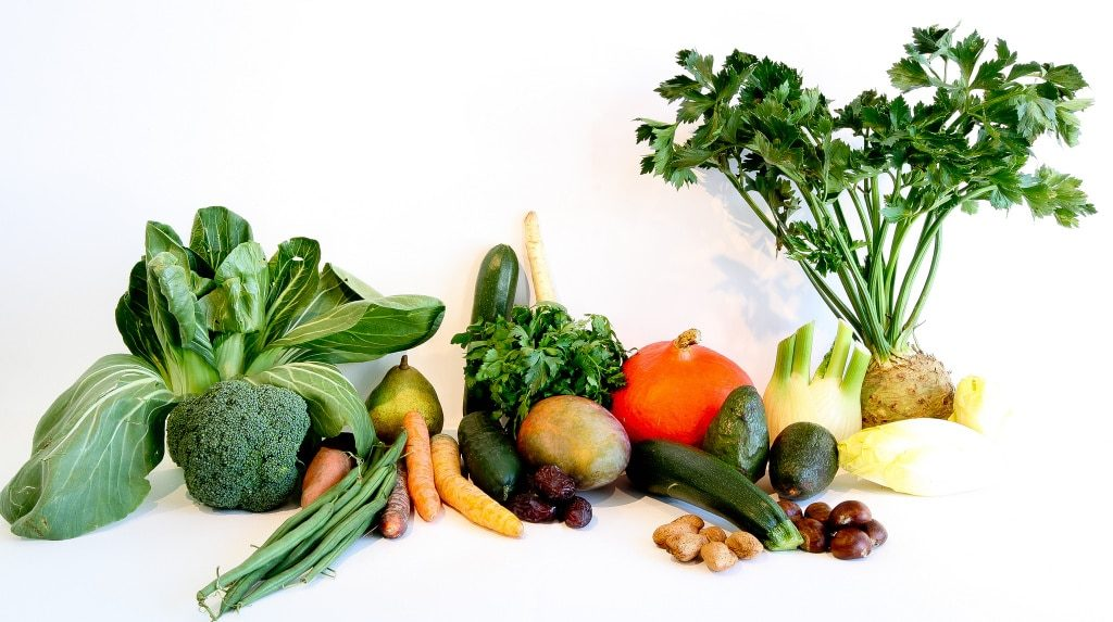 A collection of vegetables is laid out on a white table against a white background. Nutrition can positively affect your hormone balance.
