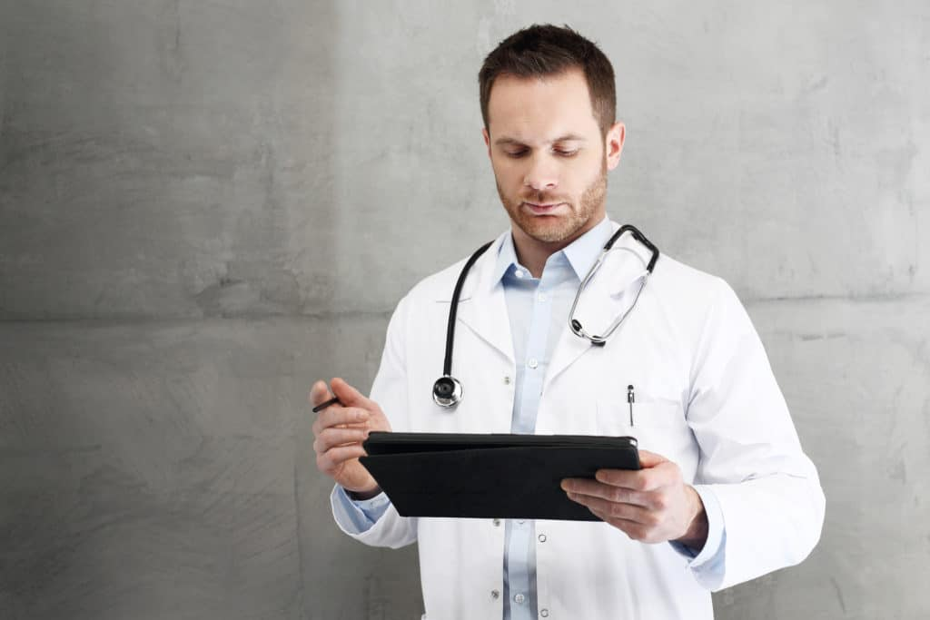 A doctor wearing a white lab coat is reading information on a tablet computer, possibly reviewing the latest research regarding TRT for men with prostate cancer history.