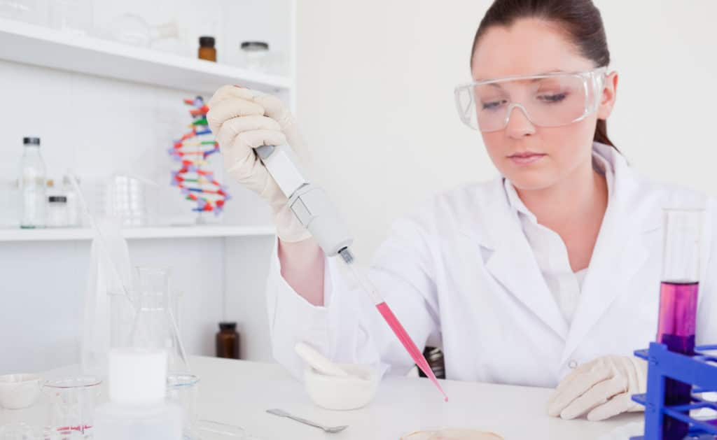 A woman wearing a white lab coat and protective eyewear examines blood in a pipette, possibly studying the connection between anemia and low testosterone.