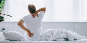 A middle-aged man wearing a white t-shirt sits on a bed with white sheets. He is facing away from the camera, holding his neck and back. Research has found a connection between osteoporosis and low testosterone levels.