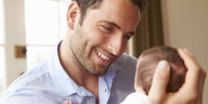 A man smiles while holding a newborn baby. Many men have questions about TRT and fertility.