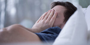 A man covers his face with his hands as he suffers from lack of sleep, possibly caused by a on of