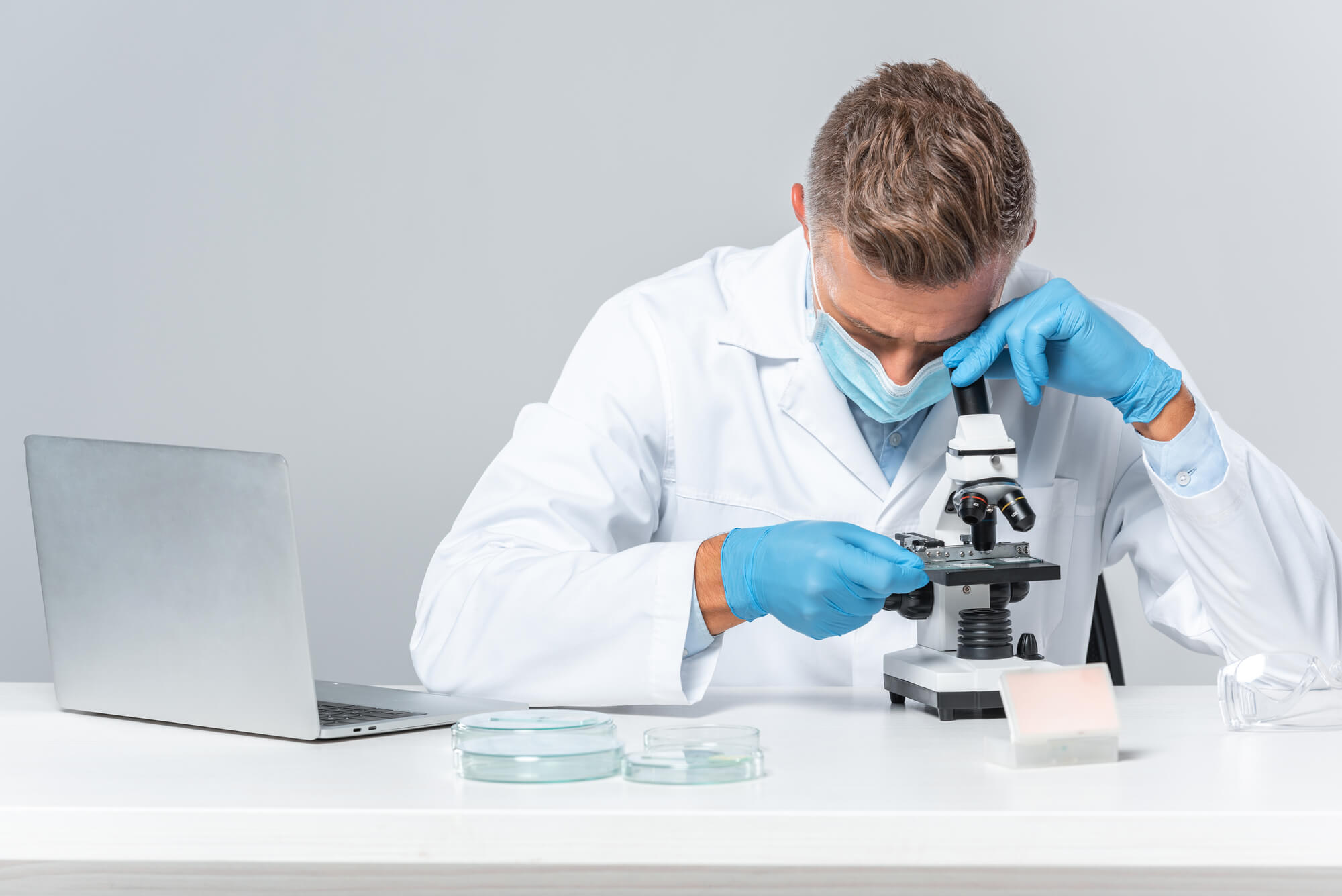 A male scientist in a white lab coat looks down into a microscope while researching the benefits and disadvantages of testosterone pellets.