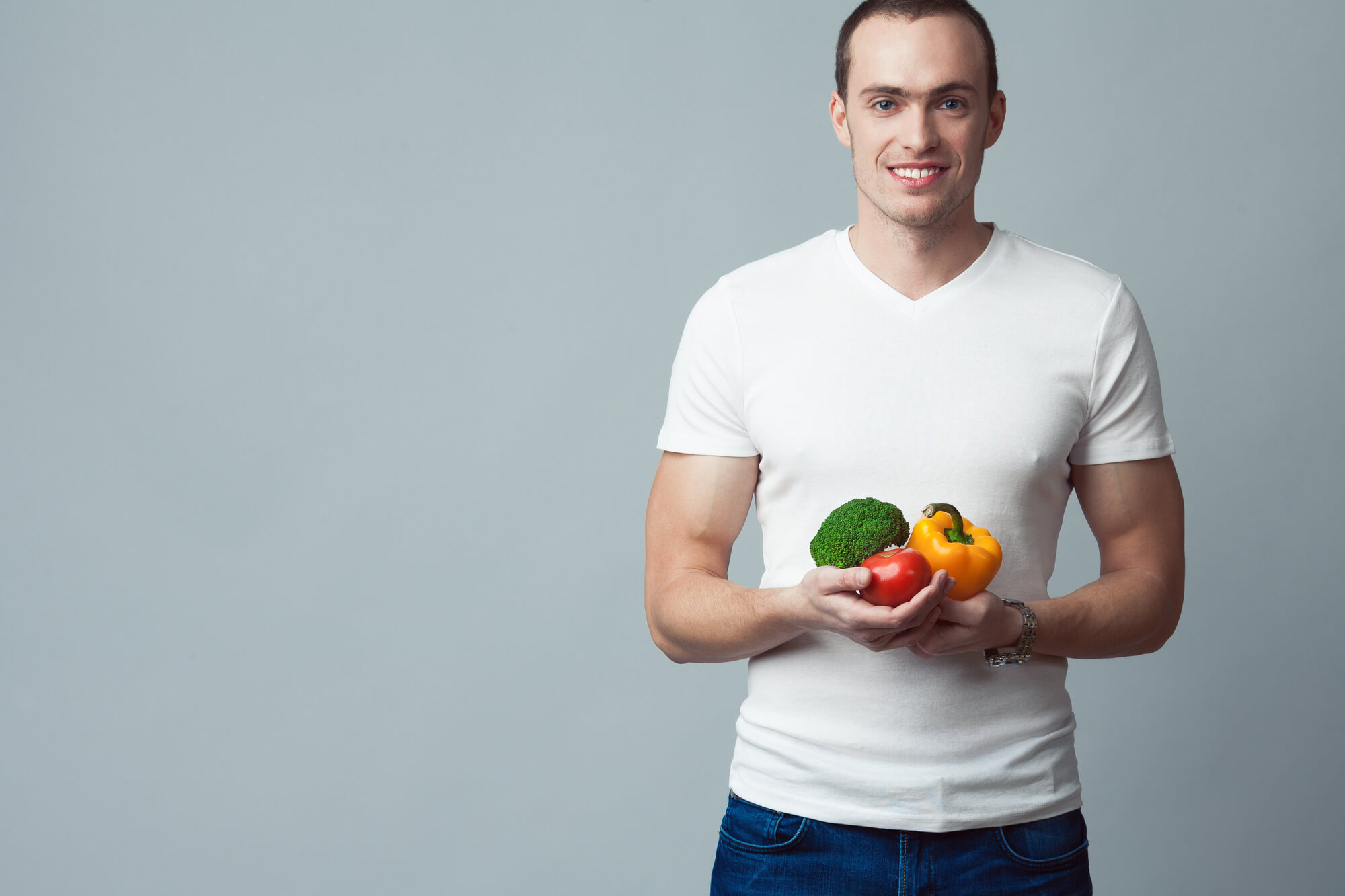 Young man in a white t-shirt holds fresh vegetables. Medical research shows that a low-fat diet can contribute to low testosterone under some circumstances.