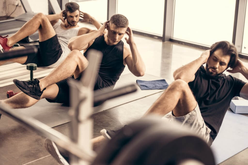 Three men are performing sit ups on the floor of a gym. Exercise is not a cure for clinical low testosterone.