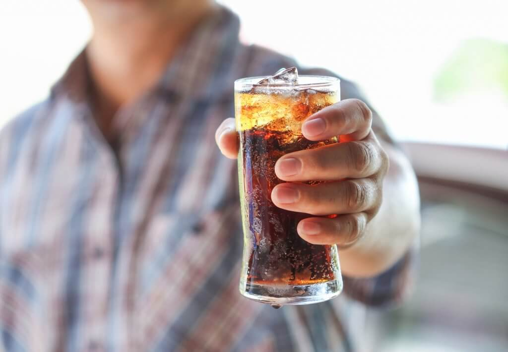A man is holding out a sugary cola. Drinking too many sugar filled beverages could contribute to low testosterone.