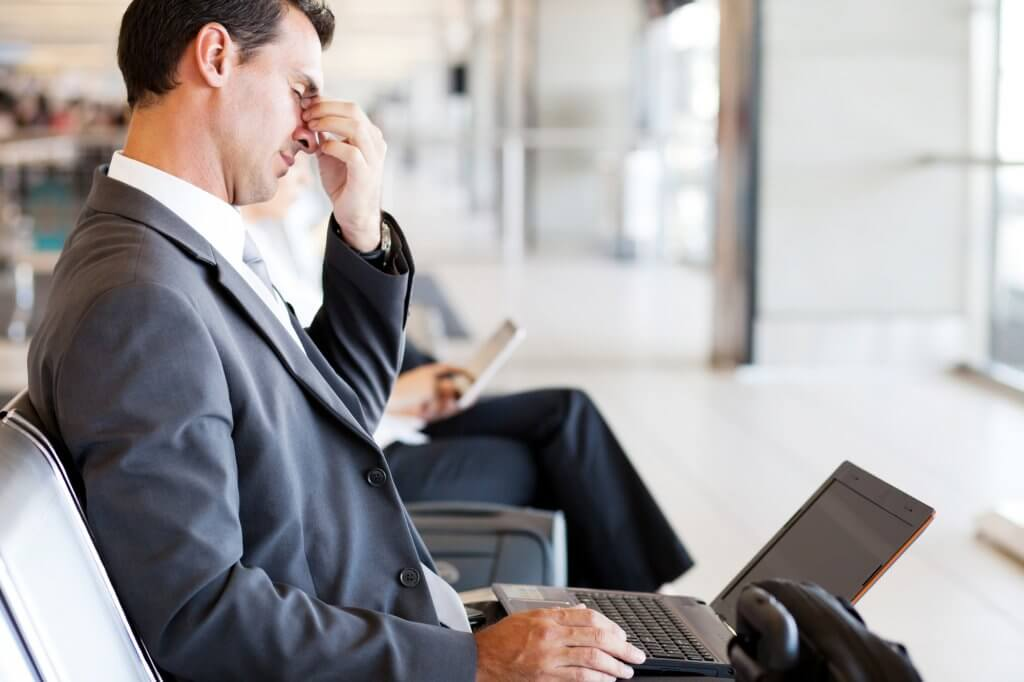 A tired businessman in a gray suit sits at an airport with a computer sitting on his lap. He is rubbing the bridge of his nose and looks fatigued. He may be suffering from the symptoms of male hypothyroidism.