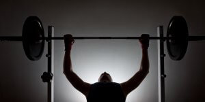 A silhouette of a man performing the bench press. Estrogen blockers are the latest method of doping for performance enhancement.
