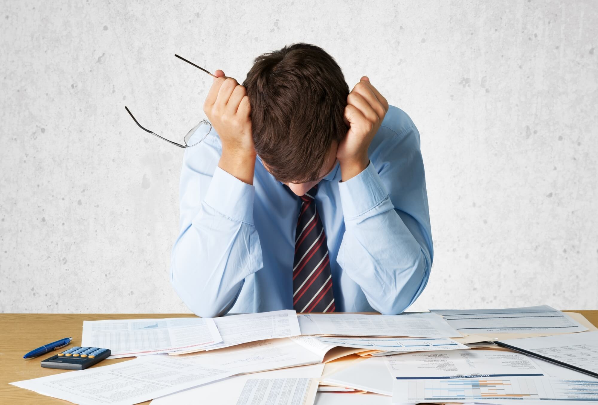 A man sits at a table covered in paper files and charts. He is wearing a blue shirt with a striped tie, and he has his head in his hands. He looks frustrated, possibly due to the connection between hormones and anxiety.