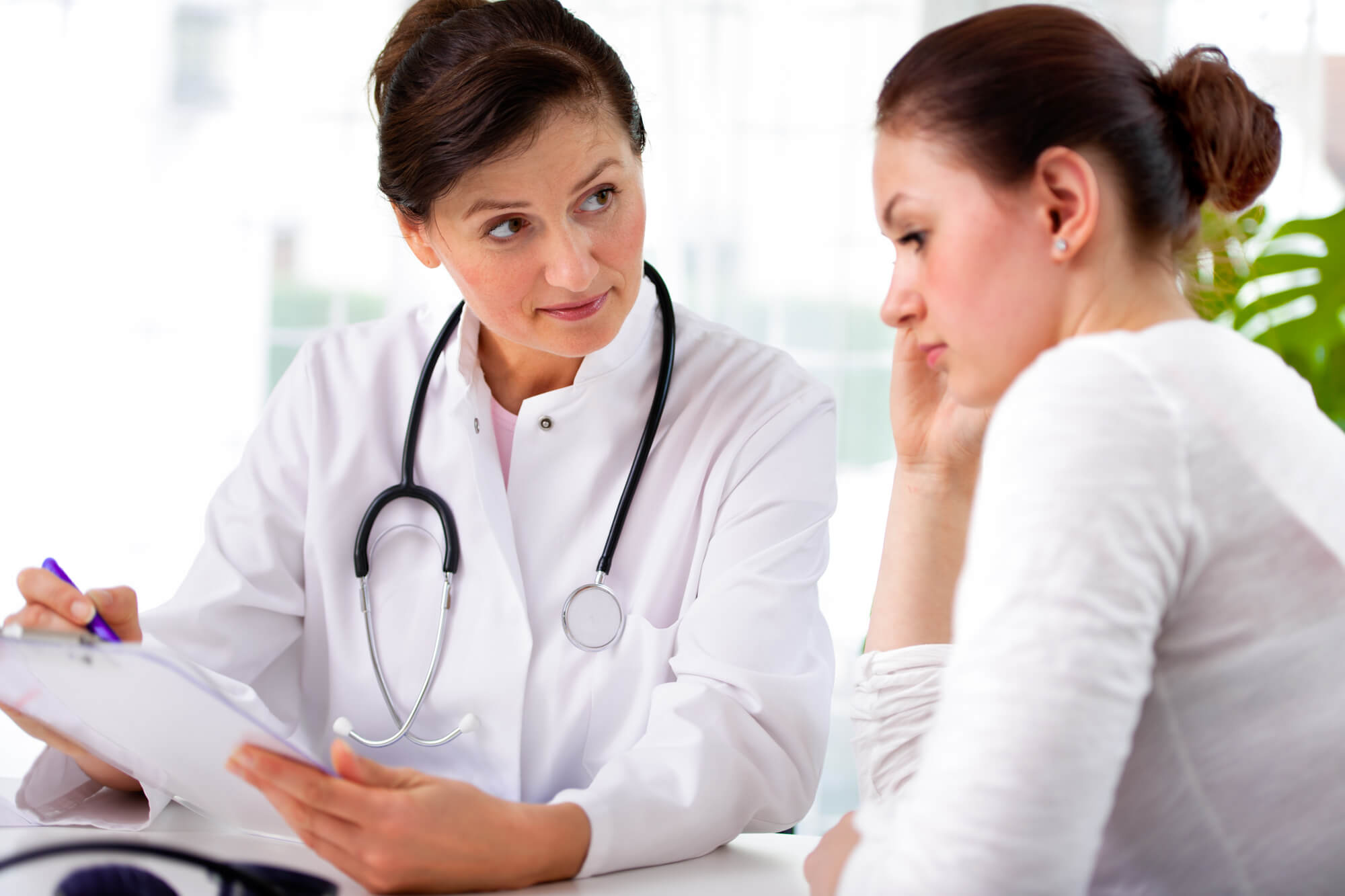 A female doctor with a stethoscope around her neck explains the benefits of DHEA to her female patient.
