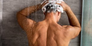A rear view of a man's upper body as he shampoos his hair in the shower. He is likely unaware of the parabens in the shampoo that could contribute to low testosterone.