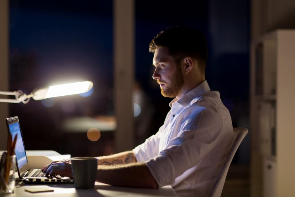 A shift worker sits at his desk at night. Shift work has been connected to low testosterone.
