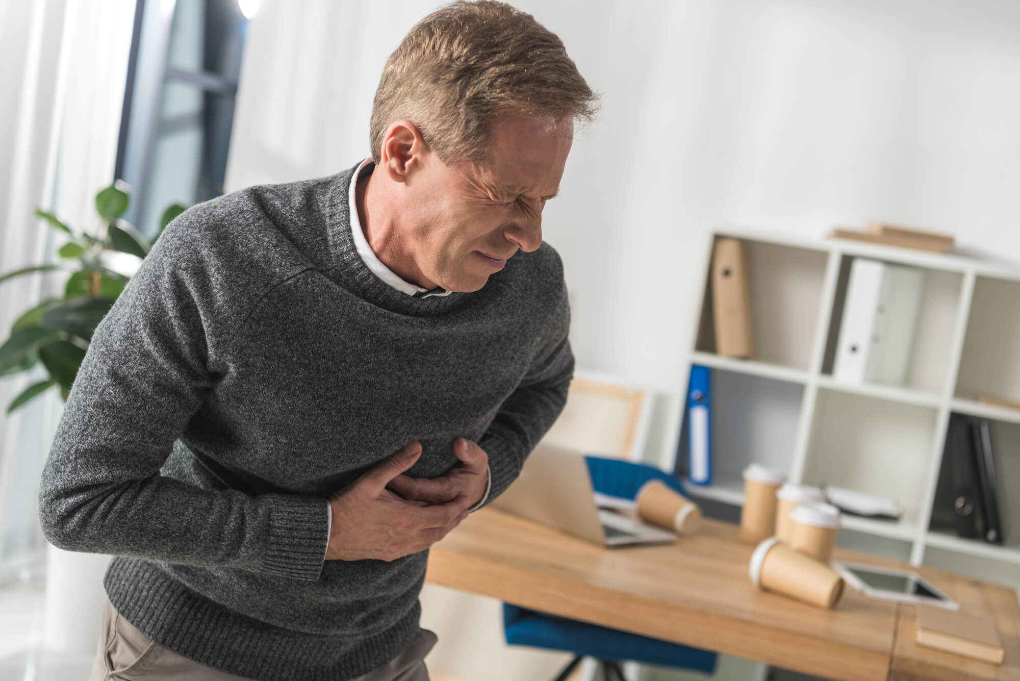 A man in a gray sweater clutches his chest, apparently from a heart attack. Research shows TRT is likely not the cause.