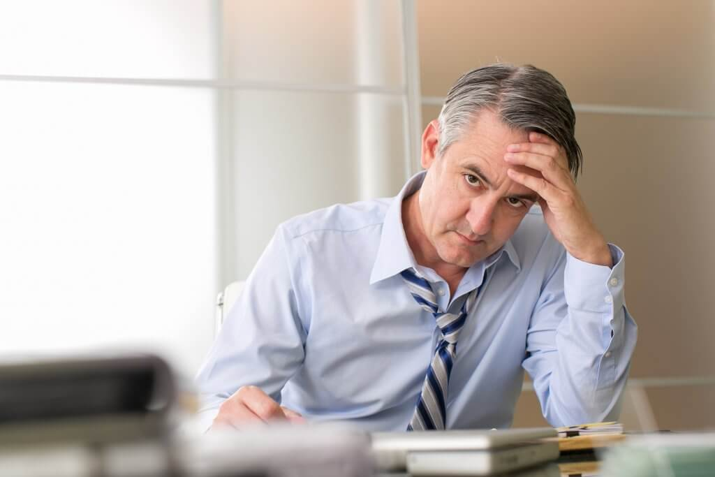 A man in a blue work shirt and striped tie sits at a desk with his head resting on his hand. His high level of stress may be causing low testosterone.