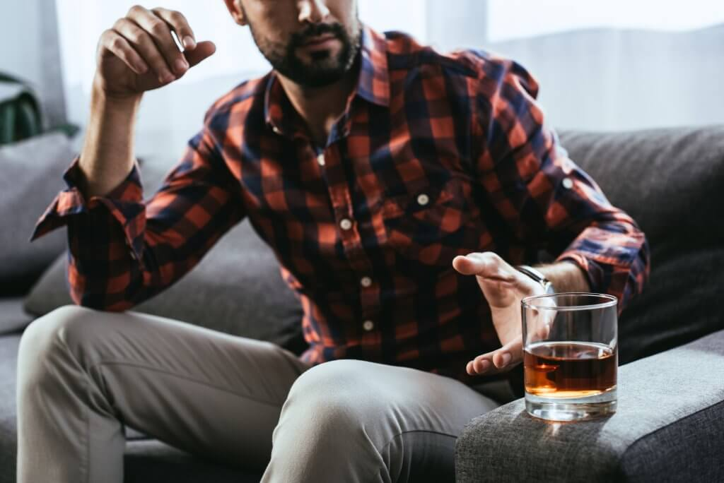 Man with a beard and plaid shirt reaches from the sofa to pick up a tumbler of alcohol, which can cause low testosterone when consumed to excess.