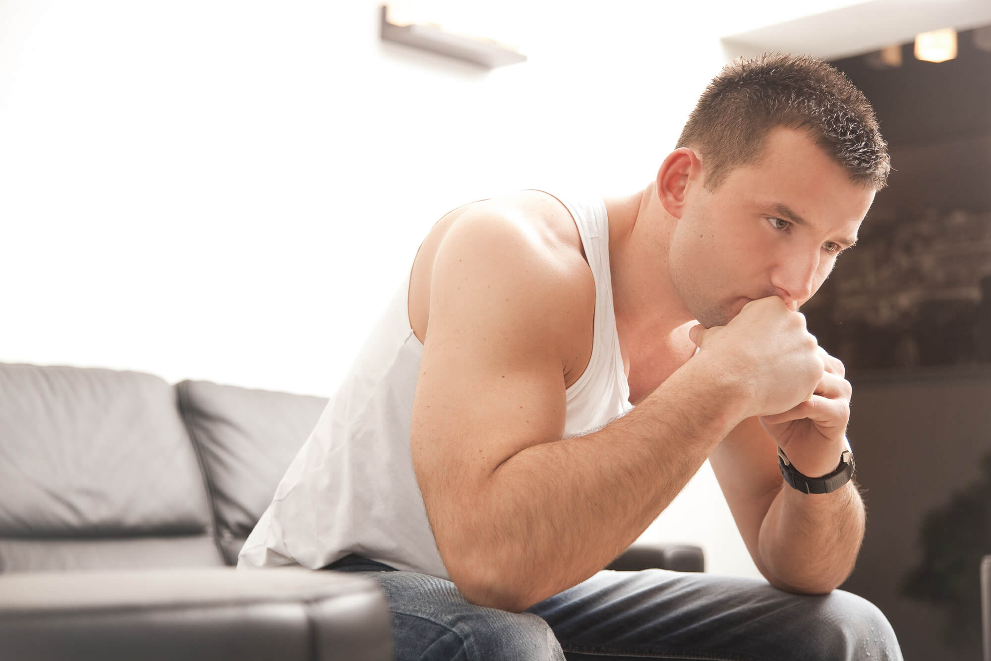 A man in a white tank top sits on a sofa with his chin resting on his hands. He looks worried, and his mood may be affected by low testosterone.